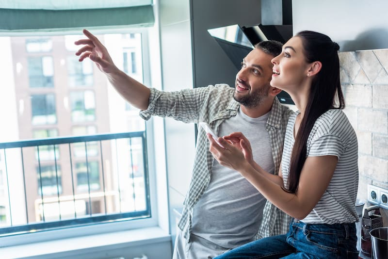 couple in apartment with smartphone copy